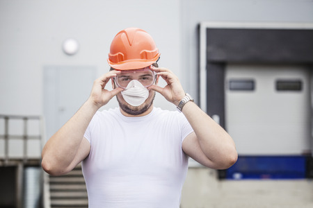safety mask: Builder male worker in protective mask and glasses in the helmet. Construction, safety, performance.