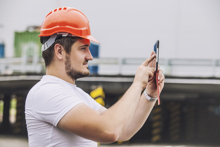 Builder man working with a tablet in a protective helmet. Construction, safety, performance. Foto de archivo