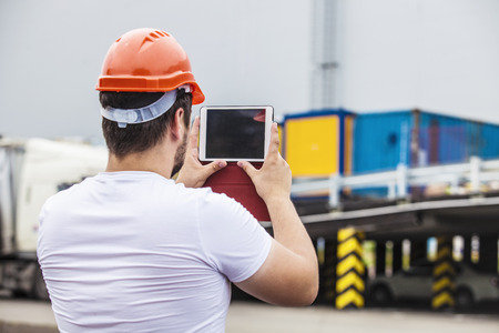Builder man working with a tablet in a protective helmet. Construction, safety, performance. Standard-Bild