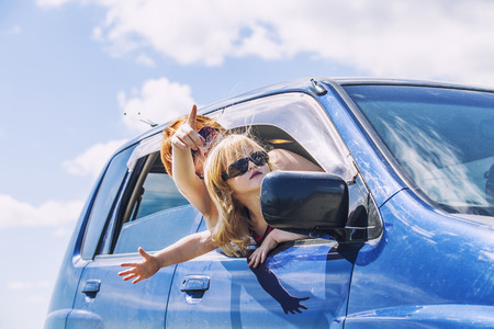 Mother and daughter in the car with sunglasses are traveling riding on a background cloudy sky. Vacation, trip, summer, tour, family, happiness