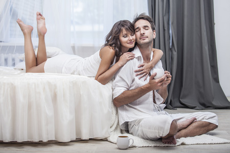 Couple man and woman at home in bed with a Cup of coffee. Love, family, relationships, tenderness