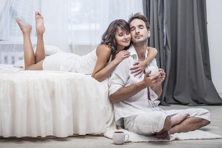 pareja en la cama: Pareja hombre y una mujer en su casa en la cama con una taza de café. Amor, familia, relaciones, sensibilidad Foto de archivo
