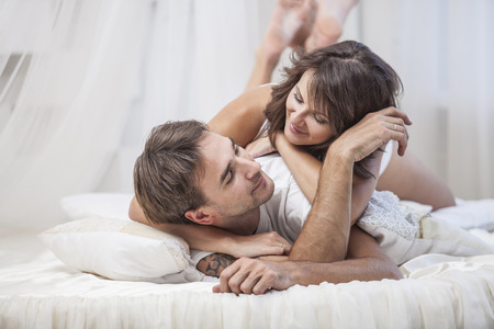 nude wife: Couple man and woman lay cuddling on the bed at home. Love, family, relationships