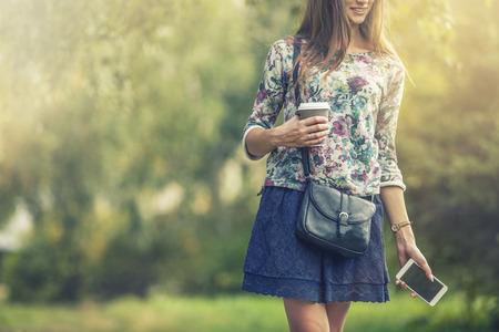 Mooie vrouw model met take-away koffie en een telefoon in het Park. Stijl,, drank, geluk, Sunny toevallige Stockfoto