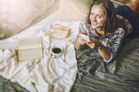 コーヒー、パン菓子、毛布の上自宅の電話に美しい女性モデルです。朝食、朝、自宅の快適さ 写真素材
