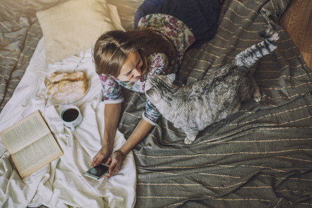 Beautiful woman model with coffee, pastries, home phone on the blanket with a cat. Breakfast, morning, home, comfort