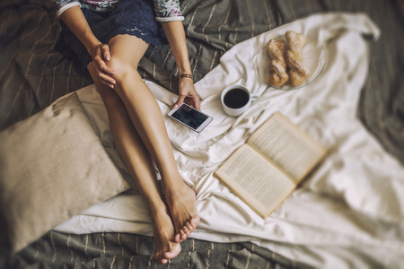 Beautiful woman model with coffee, pastries, home phone on the blanket. Breakfast, morning, home, comfort Standard-Bild