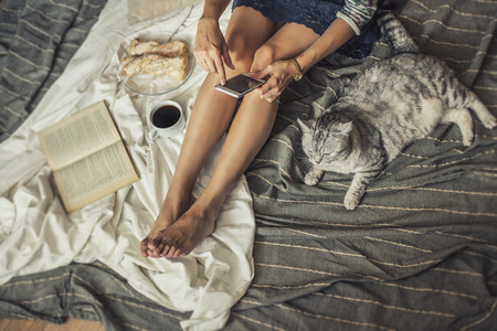 pastry: Beautiful woman model with coffee, pastries, home phone on the blanket with a cat. Breakfast, morning, home, comfort