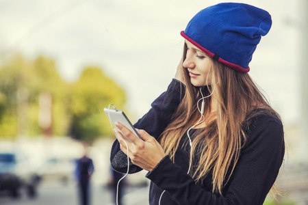 Beautiful woman model with phone and headphones on the street. Communication, music, portrait, listening, style