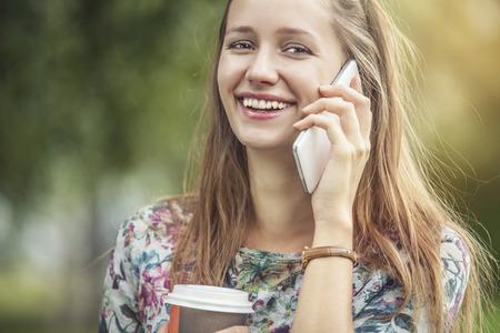 テイクアウトのコーヒーと公園内の電話美人モデル。スタイル、カジュアル、飲み、幸福、サニー