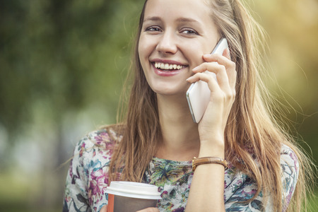 Beautiful woman model with take-away coffee and a telephone in the Park. Style, casual, drink, happiness, Sunny