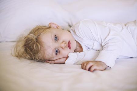 jolie fille: Petit enfant europ�enne couch� sur le lit. Blanc, triste, beau, gar�on, fille Banque d'images