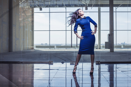 Beautiful woman in the spacious lobby with flying hair. Stylish business lady in a blue dress