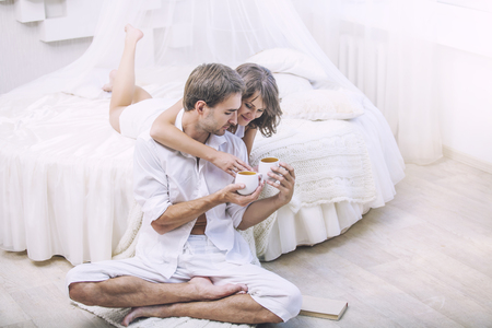 relationship love: Couple man and woman at home in bed with a Cup of coffee. Tender love in family relationships