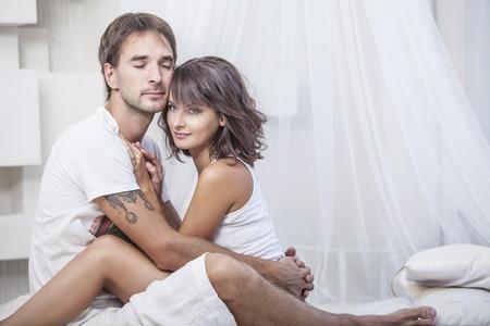 young sex: Пара мужчина и женщина лежали обнимаются на кровати у себя дома. Любовь в семейных отношениях