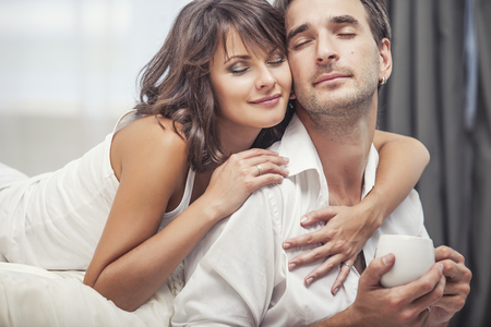 intimate: Couple man and woman at home in bed with a Cup of coffee. Tender love in family relationships