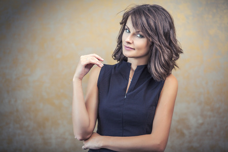 tight dress: Portrait of a woman in a black tight dress with hair and makeup on a bronze background Stock Photo