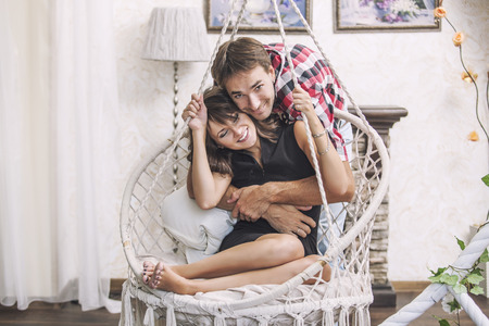 Couple man and woman in a hanging chair cuddling at home 写真素材