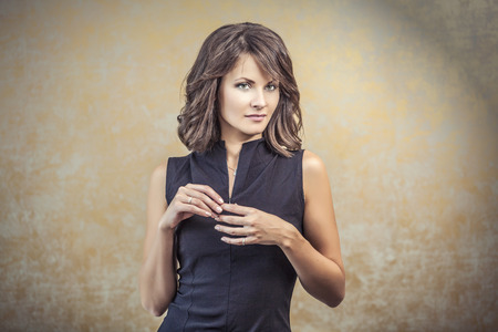evening: Portrait of a woman in a black tight dress with hair and makeup on a bronze background Stock Photo