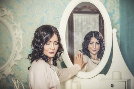 Mooie vrouw in de spiegel weerspiegelde de glimlach op magische wijze in retro interieur