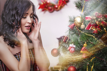 woman hanging toy: Beautiful woman in new year interior dresses up Christmas tree Stock Photo