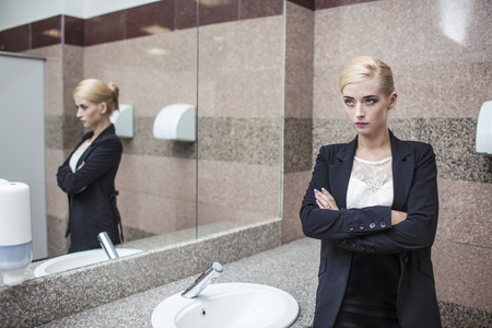 Beautiful model woman businesswoman in business attire in the mirror in the bathroom