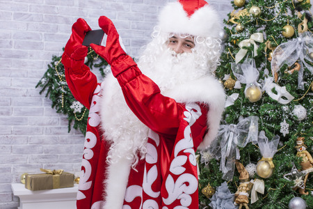 'grandfather frost': Portrait of Santa Claus who is making selfie on mobile phone on background of Christmas tree