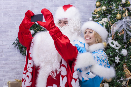 'grandfather frost': Santa Claus and snow maiden making selfie on mobile phone on background of Christmas tree