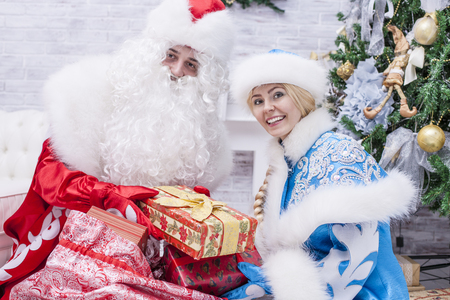 'snow maiden': Portrait of Santa Claus and snow maiden close up with gift Packed in a hand on a background of Christmas tree