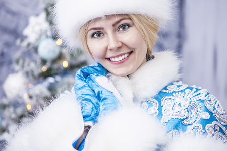 Portrait of a beautiful woman snow maiden close up in winter clothes on a background of Christmas lights