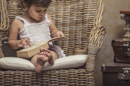 Leuk meisje kind in een stoel, een boek te lezen in retro interieur