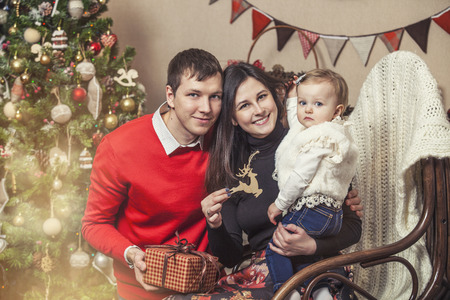 3 year old: Family mother father and children with gifts in beautiful boxes in the Christmas interior