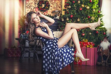 Mujer hermosa, atractiva en el fondo de la Navidad interior es elegante y de moda con el pelo y el maquillaje de lujo