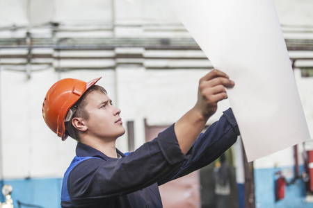 protective helmets: Young man with blueprints working on an old factory for the installation of equipment protective helmets Stock Photo