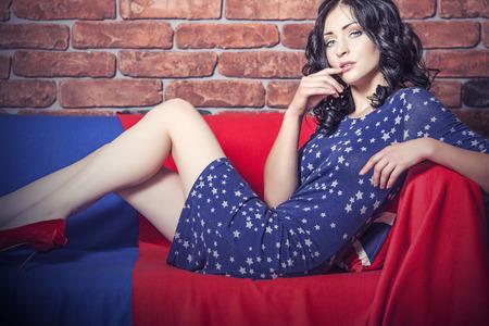 mujeres morenas: Mujer bella modelo en el sofá con el vestido en tonos azules y rojos contra una pared de ladrillo