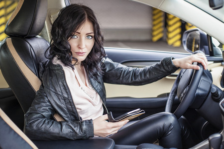 Beautiful sexy female model in leather clothes with a white car and a smartphone in the Parking lot