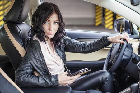 Mooie sexy vrouwelijk model in lederen kleding met een witte auto en een smartphone op de parkeerplaats Stockfoto