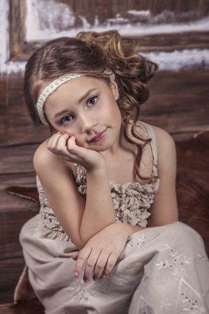 cotton dress: Little girl beautiful fashion in gentle natural cotton dress on a background of wooden wall Stock Photo