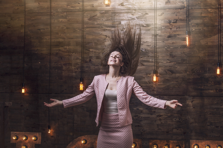 woman flying: Beautiful young fashion woman in suit with flying hair, arms outstretched free and happy