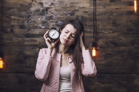 constraints: Beautiful young smart woman with alarm clock in hand and a sour face to indicate the concept of time constraints