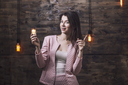 signifies: Beautiful young smart woman in a suit burning light bulb in his hand which signifies inspiration or a new idea