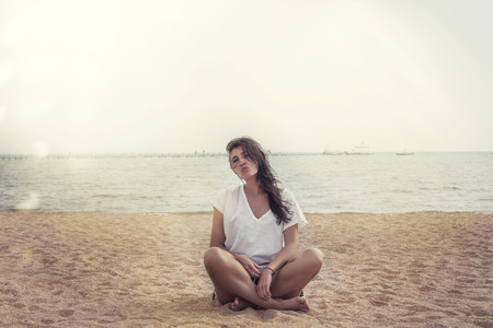 tunic: Woman in a linen tunic on the beach happy smiles and relaxes in the sunlight and the glare