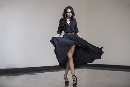 Belle femme dans la chambre au Studio danse dans une robe noire avec de longues boucles noires sur sa tête Banque d'images
