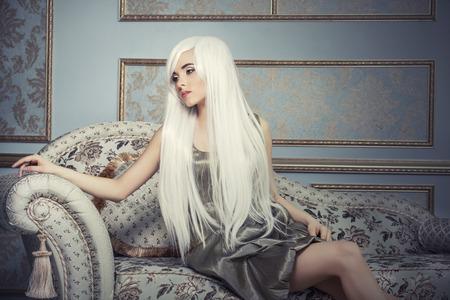 Mooie vrouw model met lange platinum witte haren tegen prachtige interieur Stockfoto