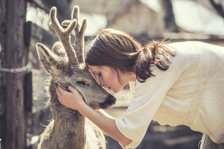 Young beautiful woman hugging animal ROE deer in the sunshine, protecting an animal