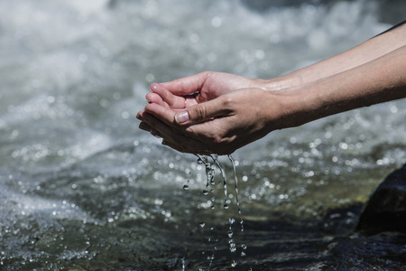 Hands sachibalaya clean water from the mountain stream bubbling Stock Photo
