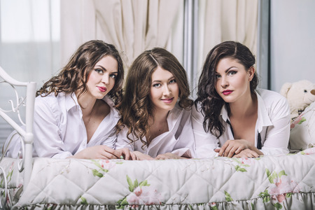 Three beautiful young women friends chatting in the bedroom in white shirts Foto de archivo