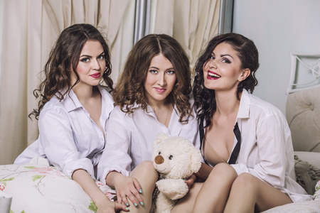 pijamada: Three beautiful young women friends chatting in the bedroom in white shirts Foto de archivo