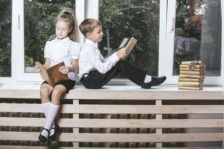 windowsill: Happy boy and girl sitting on the windowsill reading books on the background of a window into a blooming garden Stock Photo