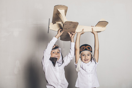 Boy and girl with wooden model airplane and a cap with cap designs in the Studio